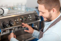 Attractive male barista is doing his job with Royalty Free Stock Images