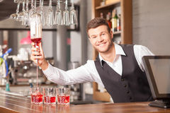 Attractive male barman is making cocktails in bar Royalty Free Stock Photography