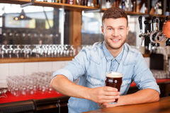 Attractive male barman is working in bar Royalty Free Stock Photo