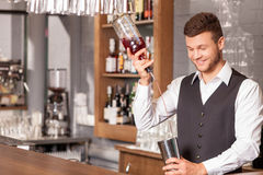 Attractive male bartender is making alcohol drink. Handsome young barman is mixing cocktail. He is holding bottle and pouring beverage into shaker. The man is Royalty Free Stock Photos