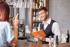 Attractive male bartender is serving female. Handsome young barman is receiving order from woman. He is holding note-book and writing down her order. The men is Royalty Free Stock Photos