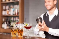 Attractive male bartender is shaking drink in pub Stock Photo
