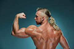 Attractive male body builder on blue background Royalty Free Stock Photo