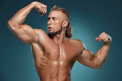 Attractive male body builder on blue background Royalty Free Stock Photography