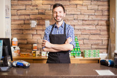 Attractive male cashier in a grocery store. Good looking young male cashier standing at the checkout counter and greeting customers with a smile Royalty Free Stock Photos