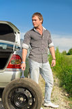 Attractive male changing tires Stock Photography