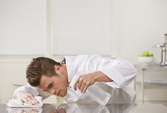 Attractive male cleaning table. Stock Photography