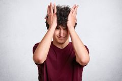 Attractive male with curly hair, wears casual maroon t shirt, has unhappy expresions, touches his head with hands  over. White background. Copy space for your stock photo