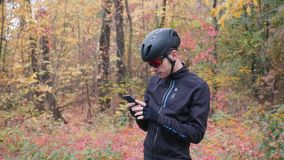 Attractive male cyclist in black helmet and sport glasses typing message on phone before cycling training on bike in fall forest. Professional triathlete stock footage