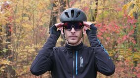 Attractive male cyclist in black helmet and warm thermo sportswear standing in fall city park and puts on sports glasses. Portrait. Of athlete guy puts on stock video