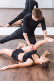 Attractive male dancer helping his partner with stretching Stock Image