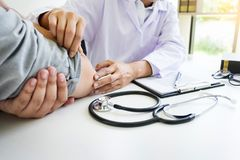 Attractive Male doctor Examining discussing reports with Massage patient suffering from back pain clinic. Attractive Male doctor Examining discussing reports royalty free stock image