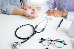 Attractive Male doctor Examining discussing reports with Massage patient suffering from back pain in clinic. Attractive Male doctor Examining discussing reports stock images