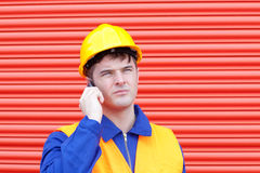 Attractive male engineer talking on the phone. In front of a garage Stock Photography
