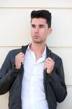 Attractive male fashion model holding black leather jacket Royalty Free Stock Photo
