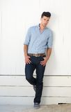 Attractive male fashion model standing against white wall outdoors Royalty Free Stock Photo
