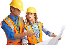 Attractive male and female construction workers looking at blue Stock Image