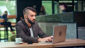 Attractive male freelancer programmer making business chatting typing using laptop at cozy cafe. Interior medium shot. Enthusiastic fashion man having online stock video
