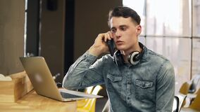 Attractive male in his 20`s in denim shirt with wireless headphones around his neck and laptop beside him, talking with. Someone on the phone. Open co-working stock video footage