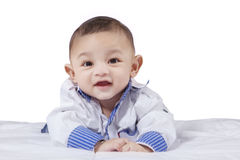 Attractive male infant laughing on bed Stock Image