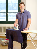 Attractive male ironing his shirt Royalty Free Stock Photography