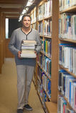 Attractive male librarian carrying a pile of books. Looking at camera Stock Photos