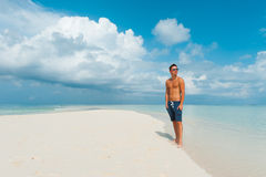 Attractive male looks around standing on beautiful beach with wh Stock Photography