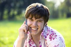 Attractive male with mobile. Very attractive young man using a mobile phone, nature background Stock Photos