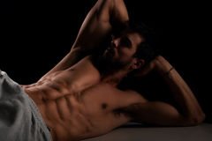 Attractive male model lying on bench Stock Images