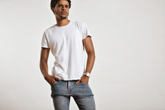 Attractive male model presenting blank white t-shirt. Portrait of a sensual black young model in unlabeled white t-shirt, light blue jeans and wearing a vintage Stock Photos