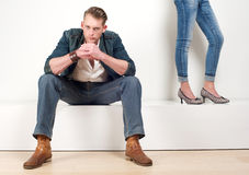 Attractive male model sitting with a pair of female legs on the side Stock Photo