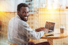 Attractive male person turning head on camera. Feeling happiness. Smiling Afro-American sitting in semi position and keeping hands on the keyboard while being at Stock Image