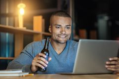 Attractive male person using his laptop. Have good plan. Delighted man expressing positivity and holding bottle in right hand while going to drink beer Royalty Free Stock Photos