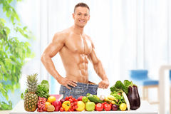 Attractive male posing behind a table with vegetables Royalty Free Stock Photos
