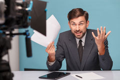 Attractive male reporter is expressing shock and. Professional young tv newscaster is evincing resentment concerning documents. He is holding papers and looking Stock Photography