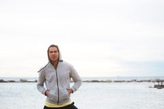 Attractive male runner dressed in sweatshirt standing on sea horizon background. Portrait of sporty caucasian man resting during his training on the beach while Stock Photos