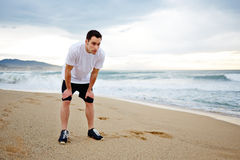 Attractive male runner dressed in the white t-shirt rest standing on the beach looking away. Morning jog, fitnes and healthily lifestyle, sport and health stock photography