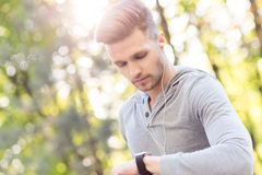 Attractive male runner using tracker Royalty Free Stock Photos