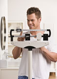 Attractive male on scale. Stock Photography