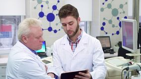 Male scientist shows something on his tablet to his coworker at the laboratory. Attractive male scientist showing something on his tablet to his coworker at the royalty free stock image