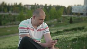 Attractive male sidia in a city park on a summer day uses the Internet with a smartphone. An attractive bald man sitting in the city park on a summer day using stock footage