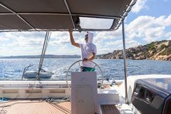 Attractive male skipper navigating the fancy catamaran sailboat on sunny summer day on calm blue sea water. Luxury summer adventure, active nautical vacation Stock Images
