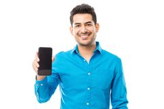Attractive Male Smiling While Holding Smartphone. Portrait of attractive male smiling while holding smartphone against white background royalty free stock images