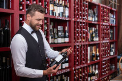 Attractive male sommelier is working in shop. Cheerful young wine waiter is standing in liquor store. He is holding a bottle of red wine. The man is looking at stock photography