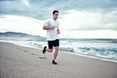 Attractive male sportsman running along the beach on the beautiful sea background. Morning jog, fitnes and healthily lifestyle, sport and health concept royalty free stock photo