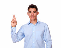 Attractive male standing and crossing fingers Royalty Free Stock Photography