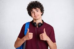 Attractive male student with crisp hair, wears casual t shirt, shows okay sign, carries rucksack, listens music via headphones, lo. Oks happily at camera Stock Images