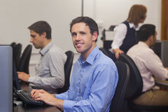 Attractive male student sitting in computer class Stock Images