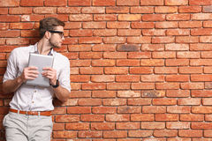 Attractive male student using modern gadget. Smart young man is standing and holding a tablet. He is leaning on wall and looking aside with seriousness. Copy Royalty Free Stock Images