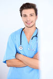 Attractive male surgeon doctor standing near the wall, crossed arms.  Royalty Free Stock Photo